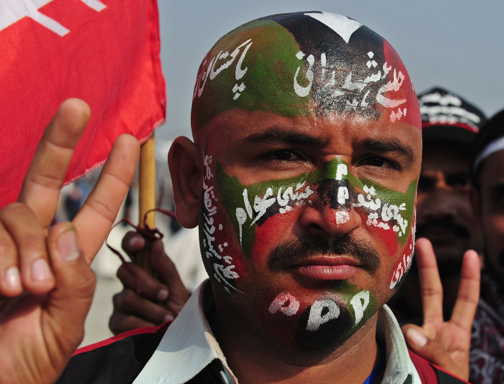 Description of . An activist of the ruling Pakistan People's Party (PPP) shows a victory sign with painted party flag on his face outside the Bhutto family mausoleum in Garhi Dera Bakhsh on December 27, 2012, on the fifth anniversary of the assassination of Benazir Bhutto.  More than 200,000 people gathered at the family mausoleum in Garhi Dera Bakhsh in the southern province of Sindh to pay their respects and to hear Bilawal Bhutto Zardari, the son of Benazir and of President Asif Ali Zardari, make his first major public speech.  AFP PHOTO/Rizwan  TABASSUM/AFP/Getty Images