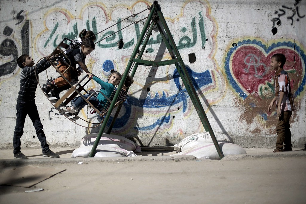 """. Palestinians children play on a swing during the second day of Eid al-Adha or \""""Feast of the sacrifice\"""" in Gaza City on October 16, 2013.  AFP PHOTO/MOHAMMED  ABED/AFP/Getty Images"""