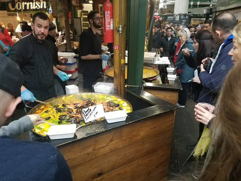 man selling paella in food stall