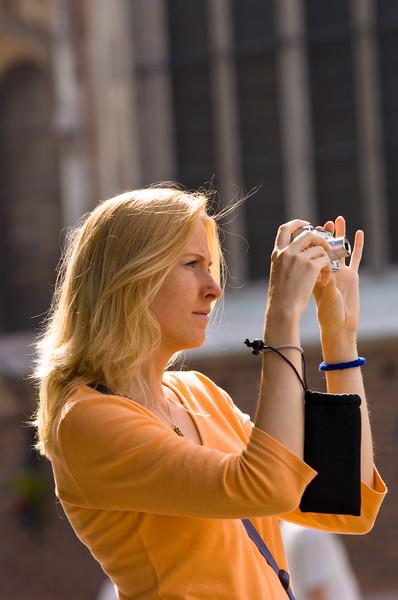 Poland, Cracow, tourist with a camera on Rynek Glowny