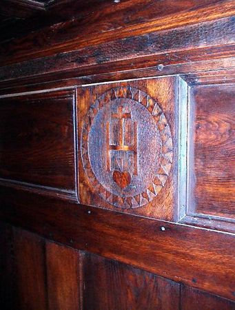 Guest room - Detail of the coat-of-arms carved into the central panel of the headboard. A similar carving is found in the central panel of the overhead canopy.