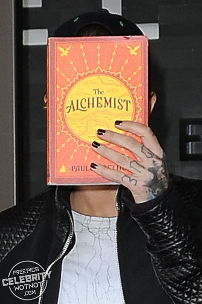 Ruby Rose Covers Her Face With The Alchemist Novel at LAX