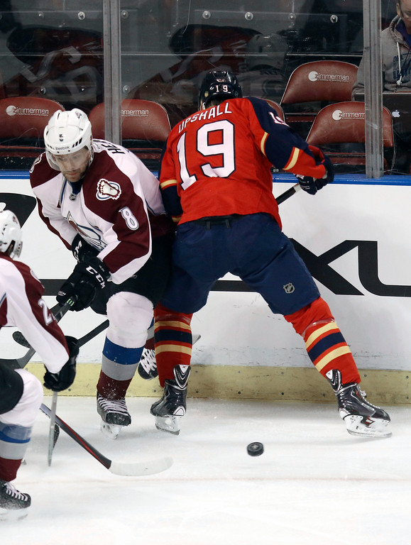 . Colorado Avalanche\'s Jan Hejda (8) and Florida Panthers\' Scotttie Upshall (19) battle for the puck during the first period of an NHL hockey game, Thursday, Jan. 15, 2015 in Sunrise, Fla. (AP Photo/J Pat Carter)