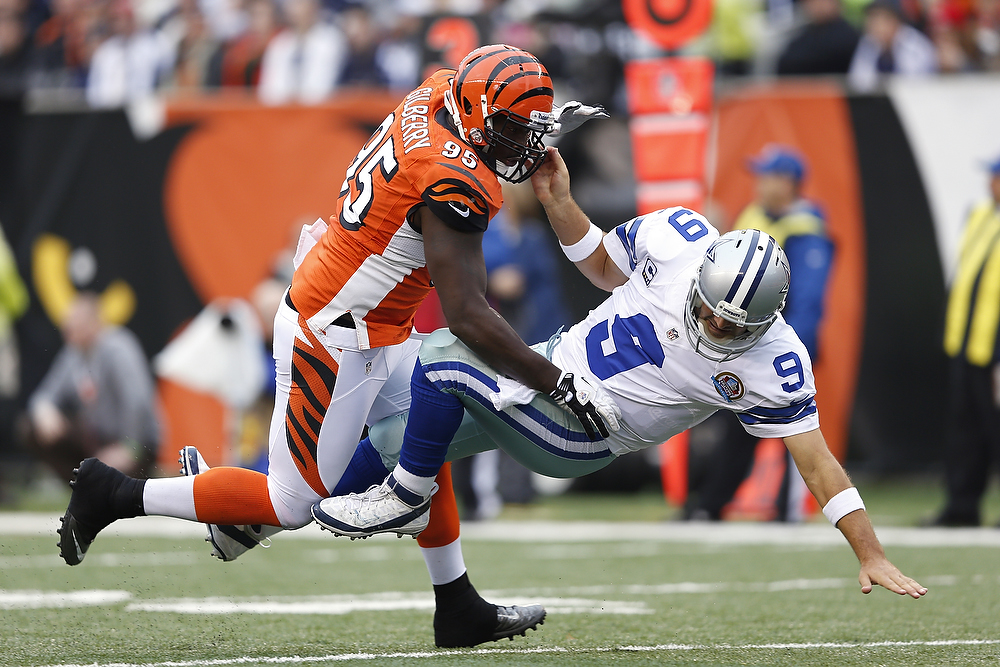 . Wallace Gilberry #95 of the Cincinnati Bengals knocks down Tony Romo #9 of the Dallas Cowboys during the game at Paul Brown Stadium on December 9, 2012 in Cincinnati, Ohio. (Photo by Joe Robbins/Getty Images)