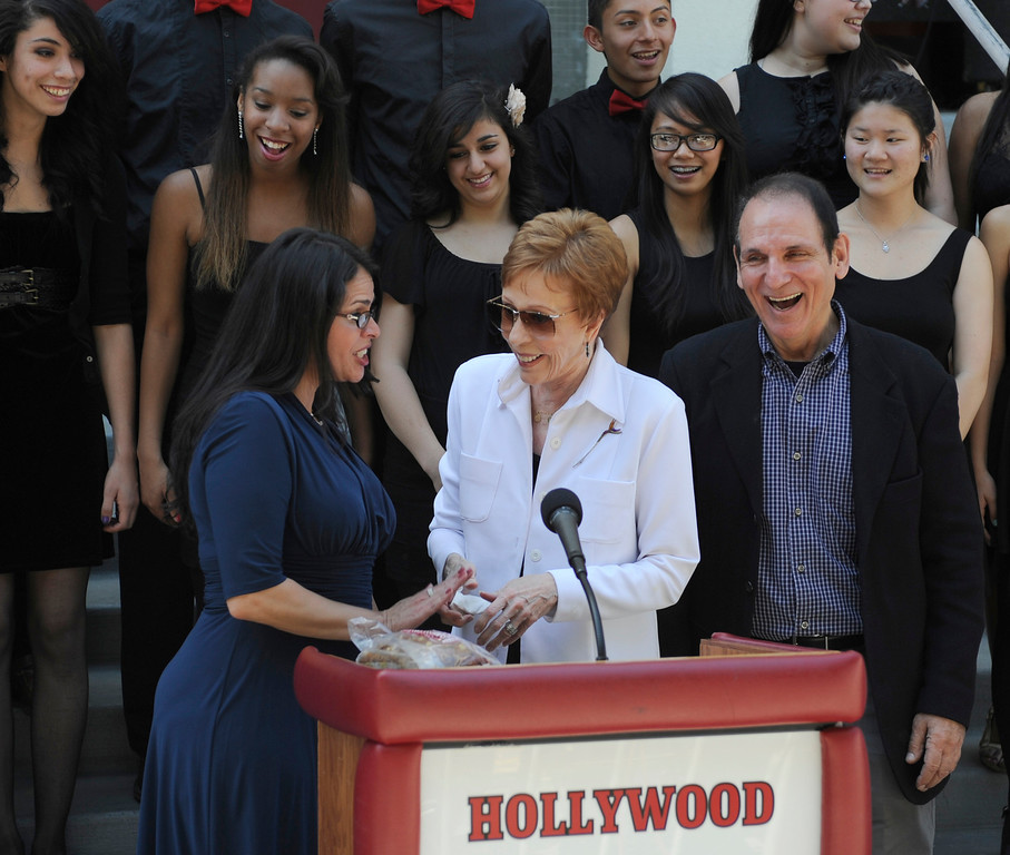 """. Hollywood High School Principal Alejandra Sanchez, Carol Burnett and director of the performing arts magnet Story Sacks. Burnett, award-winning actress, comedienne and best-selling author, was honored by the City of Los Angeles for her lifetime achievements with the naming of Carol Burnett Square at the intersection of Highland Avenue and Selma Avenue. The Square is adjacent to Hollywood High School where Burnett attended. Students from the school choir, \""""H2O\"""" sang �I�m so glad we had this time together,� before Burnett and LA City Councilman Tom LaBonge unveiled her street sign. Hollywood, CA 4/18/2013(John McCoy/Staff Photographer"""