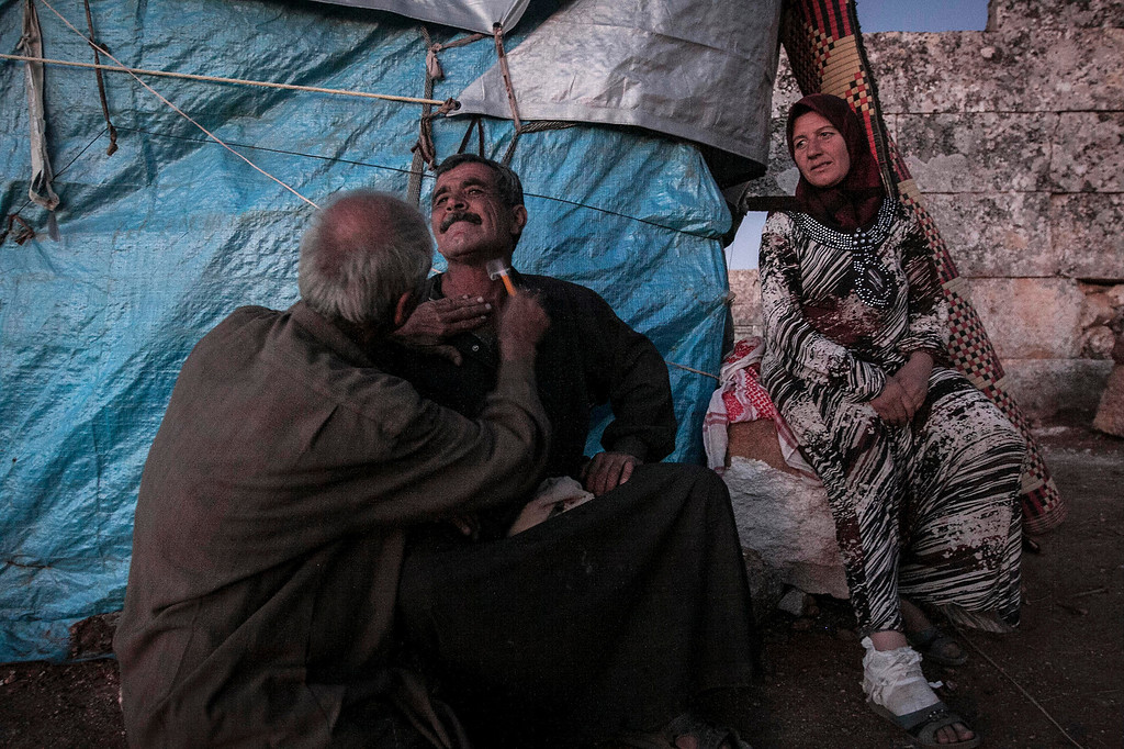 . In this Thursday, Sept. 26, 2013 photo, displaced Syrian men shave as a woman watches near Kafer Rouma, in ancient ruins used as temporary shelter by those families who have fled from the heavy fighting and shelling in the Idlib province countryside of Syria. (AP Photo)