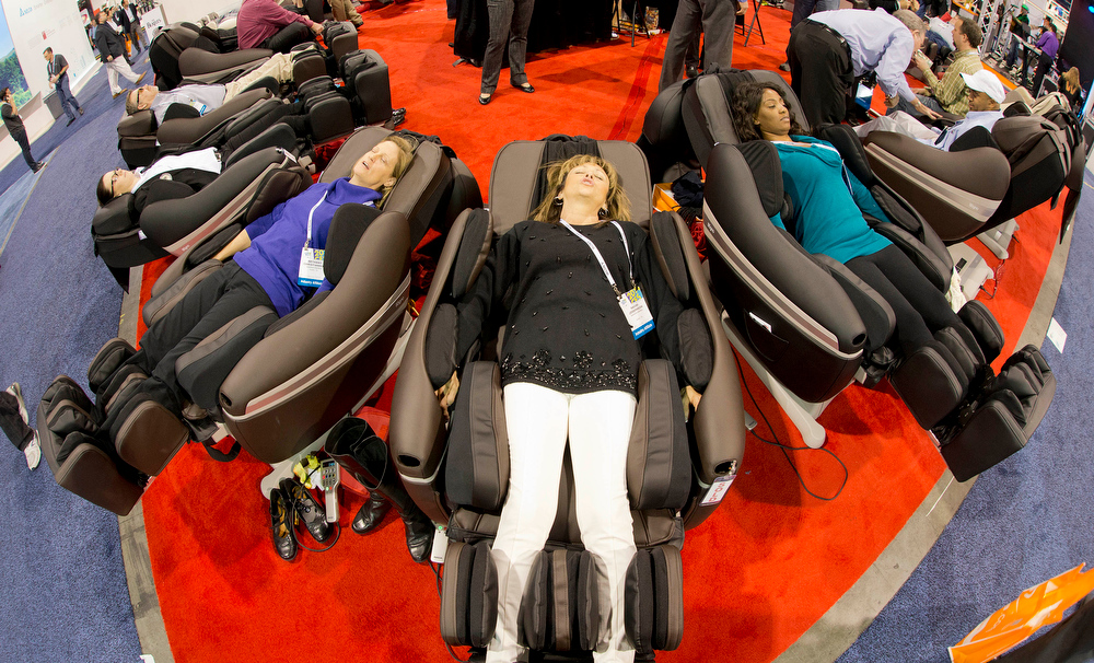 Description of . Trade show attendees relax in a display of Inada massage chairs at the International Consumer Electronics Show, Thursday, Jan. 9, 2014, in Las Vegas. (AP Photo/Julie Jacobson)