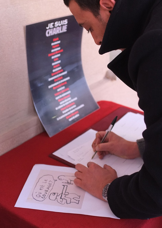 . A man signs a register of condolences for victims of the shooting at the satirical newspaper Charlie Hebdo, at Nice town hall, southeastern France, Thursday, Jan. 8, 2015. With tensions high across Paris, French authorities focused Thursday on preventing new attacks and police hunted for two heavily armed brothers _ one with a history of jihadi ties _ in the methodical killing of 12 people at a satirical newspaper that caricatured the Prophet Muhammad. (AP Photo/Lionel Cironneau)
