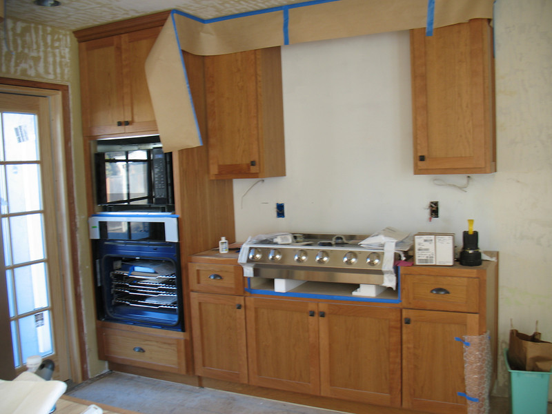 Cherry kitchen cabinets with the appliances being installed.