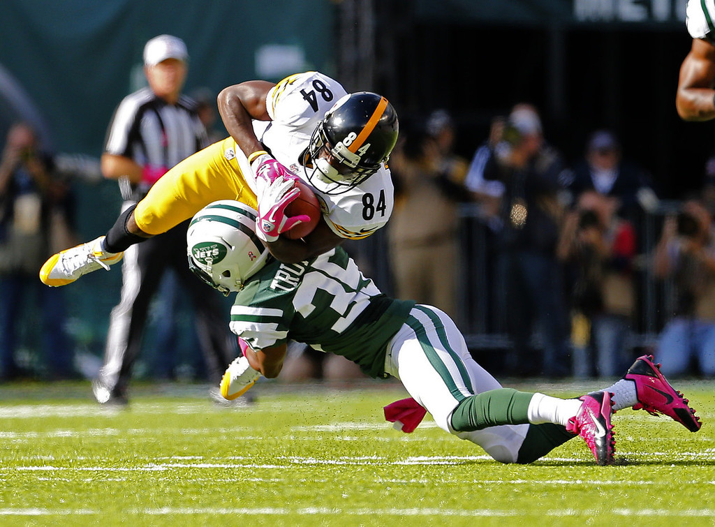 . Wide receiver Antonio Brown #84 of the Pittsburgh Steelers makes a catch and holds onto the ball as he is hit by corner back Isaiah Trufant #35 of the New York Jets in the third quarter during a game at MetLife Stadium on October 13, 2013 in East Rutherford, New Jersey. The Steelers defeated the Jets 19-6. (Photo by Rich Schultz /Getty Images)