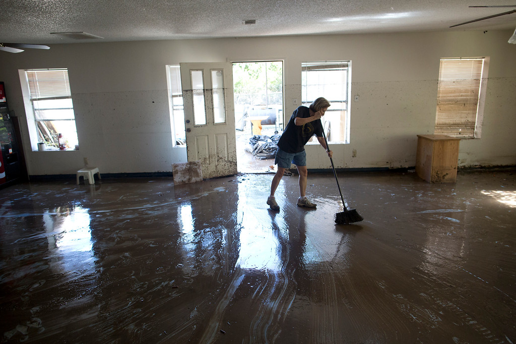 . Diana Ward helps clean up the First Independent Baptist Church after heavy rains caused water levels to rise over four feet in the church before receding on Thursday Oct. 31, 2013 in Austin, Texas. The National Weather Service said more than a foot of rain fell in Central Texas. (AP Photo/ Tamir Kalifa)