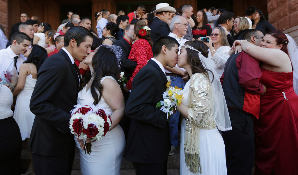 . Anthony Sanchez and Stephanie Hernandez, left, and John and Analicia Vazquez, right, kiss after taking their vows with dozens of other couples in a mass Valentine\'s Day wedding on the steps of the Bexar County Courthouse, Friday, Feb. 14, 2014, in San Antonio. (AP Photo/Eric Gay)
