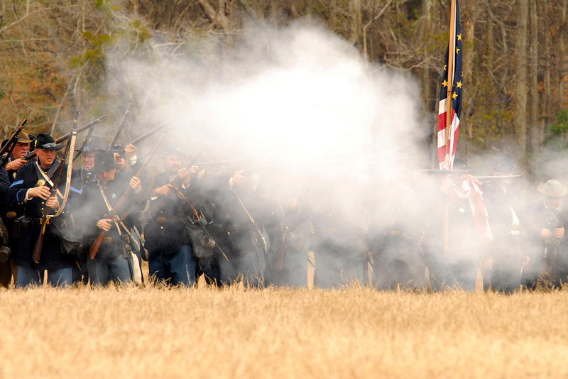 Smoke obscures the Union infantry line after the reenactors fire their weapons. The Skirmish at Gamble's Hotel happened on March 5, 1885 when 500 federal soldiers, under the command of Reuben Williams of the 12th Indiana Infantry, marched into Florence to destroy the railroad depot but were met by Confederate soldiers backed up with 400 militia. The reenactment, held by the 23rd South Carolina Infantry, was held at the Rankin Plantation in Florence, South Carolina on Saturday, March 5, 2011. Photo Copyright 2011 Jason Barnette