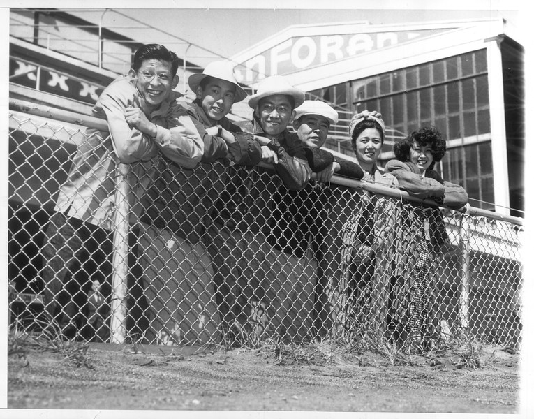 """""""Railbirds, But No Ponies to Watch -- Among the first Japanese to be moved into the newly built assembly center at Tanforan racetrack, near San Francisco, on April 28 were these, who lined up at the rail"""" -- caption on photograph"""