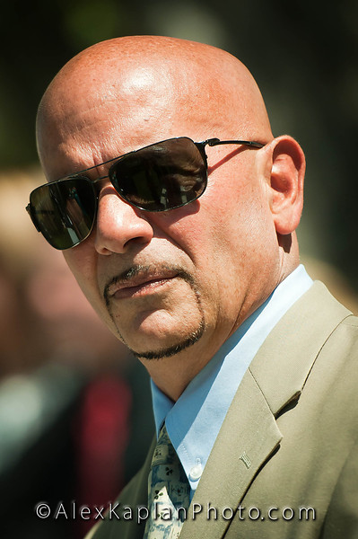 Man in a brown suit jacket with a blue shirt looking towards the camera wearing sunglasses by Alex Kaplan, Photographer http://www.AlexKaplanphoto.com