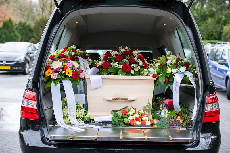 De rouwauto met de overledene en bloemen.