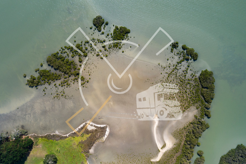 Top view of a piece of beach that runs into the water in Northland, New Zealand.