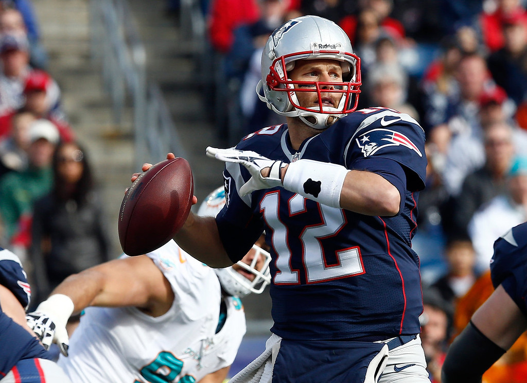 . Tom Brady #12 of the New England Patriots looks for an open man in the first half against the Miami Dolphins at Gillette Stadium on October 27, 2013 in Foxboro, Massachusetts. (Photo by Jim Rogash/Getty Images)
