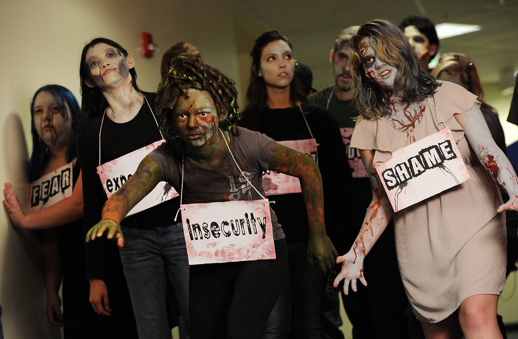 . BOULDER, CO- FEBRUARY 19:  Sydney McVicker, 14, middle and Phillipa Keosheyan, 14, right, and other Zombies walk the halls during the shooting of the video at Fairview High School in Boulder on February 19th, 2013.  With the help of a professional videographer, Fairview High School students produced a zombie video to advertise an Awareness Drive in Boulder Valley schools designed to bring attention to a variety of mental health and wellness issues.  Students were made to look like zombies by make-up artists from Theatrical Costumes, Etc. (Photo By Helen H. Richardson/ The Denver Post)
