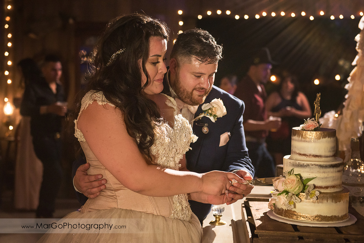 bride and groom cutting wedding cake decorated with roses at Taber Ranch Vineyards