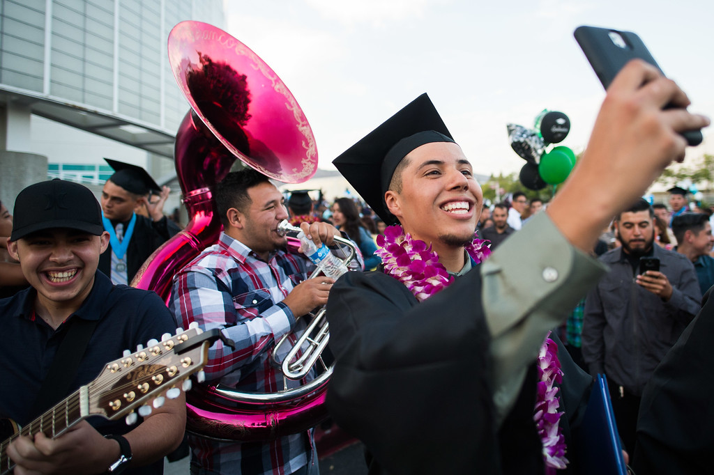 . Azusa High graduate, Alan Gomez, takes a selfie with his cousins band as they perform for him after the commencement ceremony at Azusa Pacific University Felix Event Center in Azusa on Thursday, June 4, 2015. (Photo by Watchara Phomicinda/ San Gabriel Valley Tribune)