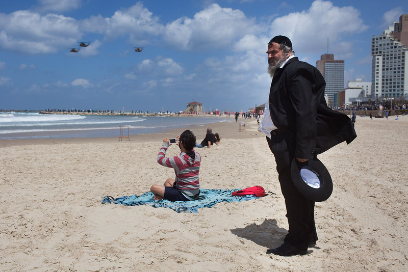 . People stand on the beach in the Mediterranean sea as they watch a military air show marking the 65th anniversary of Israel\'s independence on April 16, 2013 in Tel Aviv, Israel. The day marks when David Ben-Gurion, the Executive Head of the World Zionist Organization declared the establishment of a Jewish state in Eretz- Israel.  (Photo by Uriel Sinai/Getty Images)