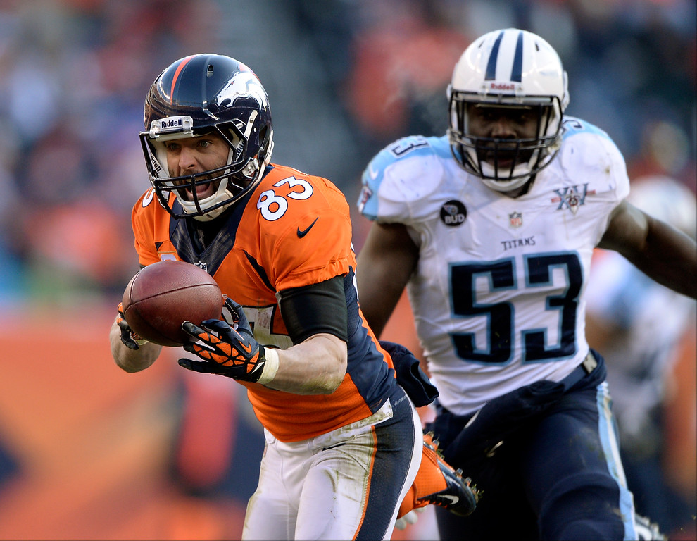 . Denver Broncos wide receiver Wes Welker (83) takes in a pass as Tennessee Titans middle linebacker Moise Fokou (53) comes in for the tackle.  (Photo by Hyoung Chang/The Denver Post)