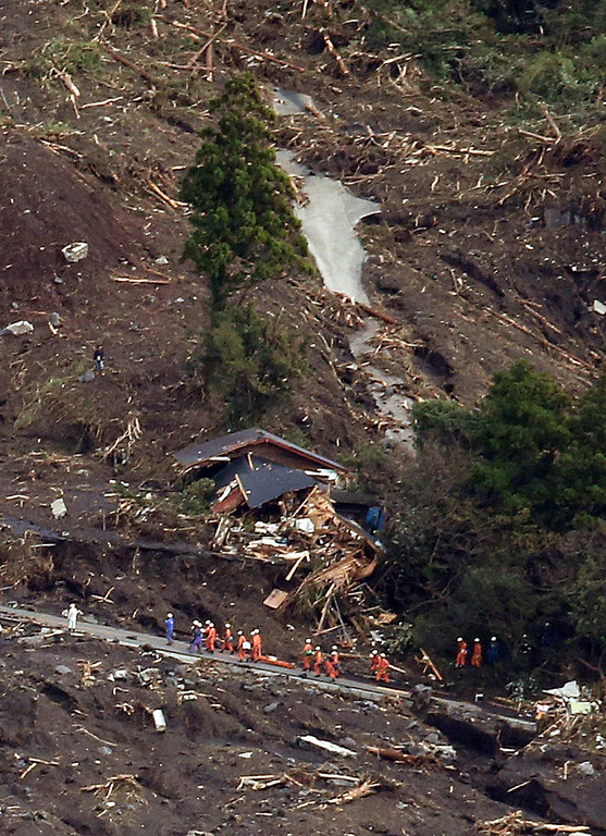 . This aerial view shows rescue workers searching for survivors after a landslide buried houses following heavy rain brought on by typhoon Wipha at Oshima island, 120km south of Tokyo on October 16, 2013.  AFP PHOTO / JIJI PRESS /AFP/Getty Images