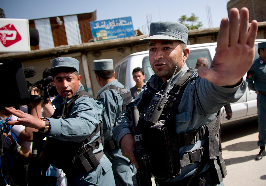 . Afghan policemen stop people from approaching the scene where a suicide car bomber attacked a NATO convoy in Kabul, Afghanistan, Thursday, May 16, 2013.  (AP Photo/Anja Niedringhaus)