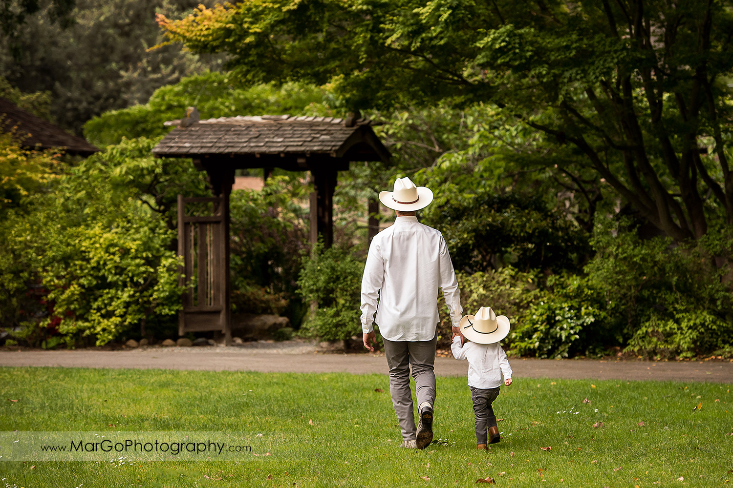 man and little boy in white shirts and cowboy hats walking on the grass in Shinn Historical Park and Arboretum in Fremont