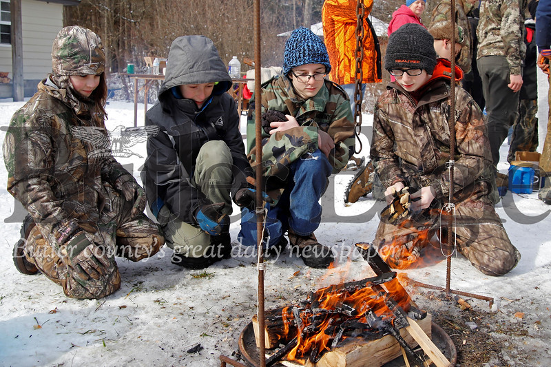Luke Bleakney (left), Moses Heine, Aaron Rape, and Ashton Wilson of combined Harmony and Ellwood City Boy Scout Troops 360 and 806 gather around the fire they built for the camp fire and water boiling competition, part of the annual Klondike Derby at Camp Buccoco near Slippery Rock. The joint troops completed the task of building a fire and boiling water in under 10 minutes. Seb Foltz/Butler Eagle 02/15/20