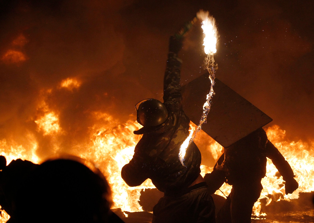 . A protester throws a Molotov cocktail onto a fire during clashes with police in central Kiev, Ukraine, early Saturday, Jan. 25, 2014. As riots spread from Ukraine\'s embattled capital to nearly half of the country, President Viktor Yanukovych promised to reshuffle his government and make other concessions - but a top opposition leader said nothing short of his resignation would do. (AP Photo/Sergei Grits, File)