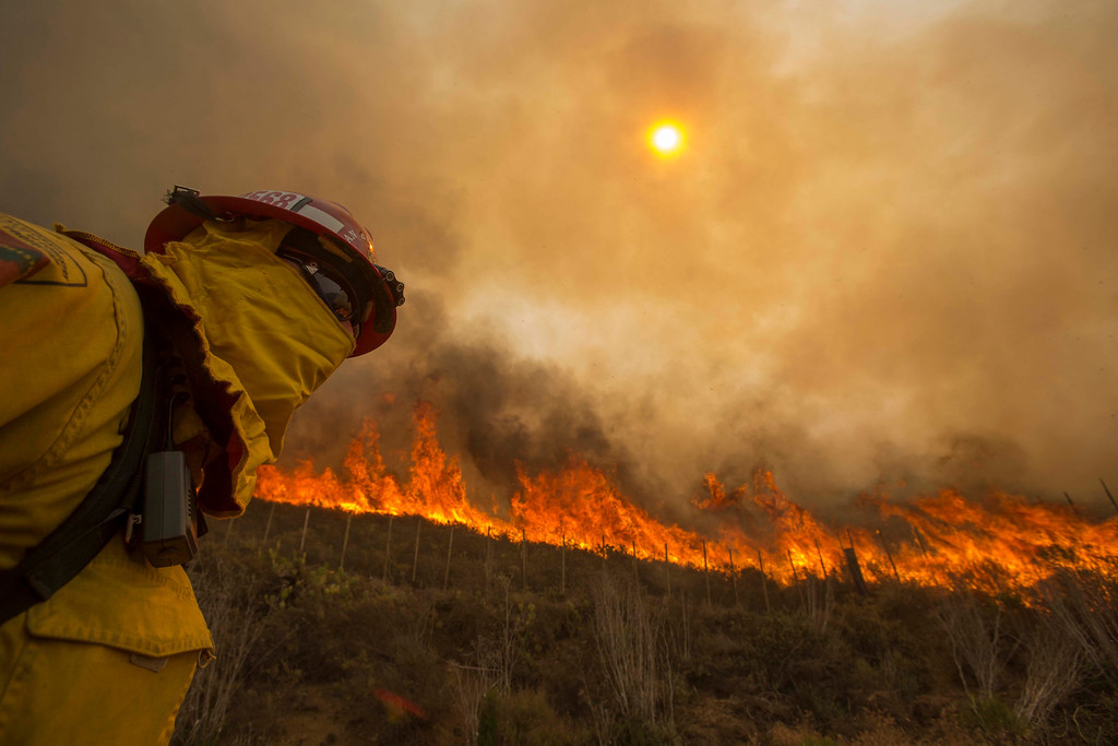 . A firefighter keeps watch as the wildfire burns along a hillside in Point Mugu , Calif. Friday, May 3, 2013. Firefighters got a break as gusty winds turned into breezes, but temperatures remained high and humidity levels are expected to soar as cool air moved in from the ocean and the Santa Ana winds retreated. (AP Photo/Ringo H.W. Chiu)