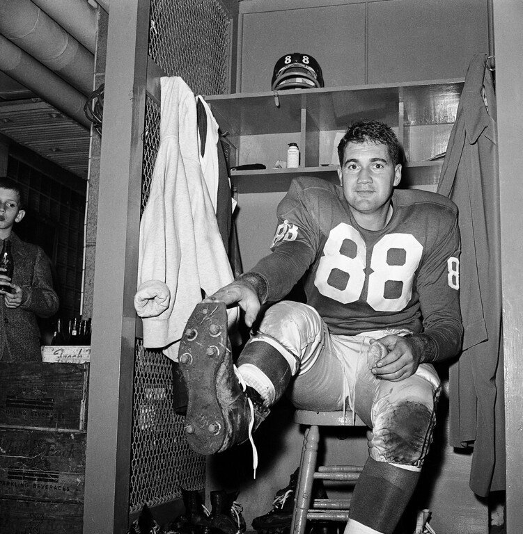 . FILE - In this Nov. 8, 1959, file photo, New York Giants place kicker Pat Summerall shows off kicking shoe for photographers in the locker room after making three field goals to help the team to a 9-3 win over the Chicago Cardinals at Yankee Stadium in New York. Fox Sports spokesman Dan Bell said Tuesday, April 16, 2013, that Summerall, the NFL player-turned-broadcaster whose deep, resonant voice called games for more than 40 years, has died at the age of 82. (AP Photo/John Lindsay, File)