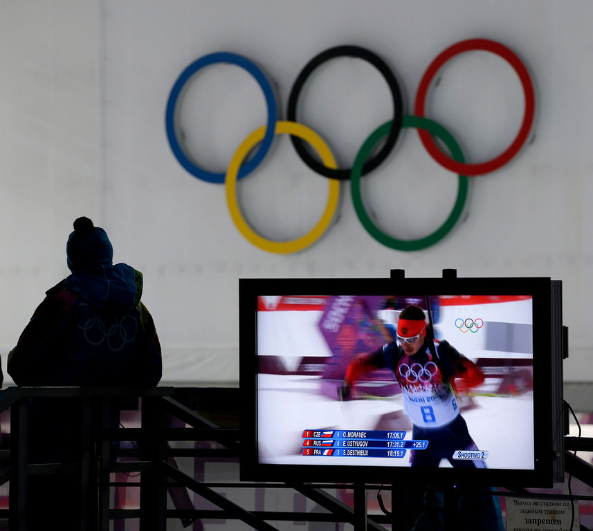 . A worker watchs the men\'s biathlon 10k sprint, at the 2014 Winter Olympics, Saturday, Feb. 8, 2014, in Krasnaya Polyana, Russia. (AP Photo/Charlie Riedel)