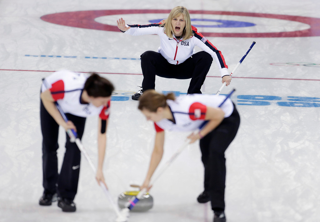 . Erika Brown, skip of the United States team, shouts instructions to her sweepers Ann Swisshelm, left, and Jessica Schultz during women\'s curling competition against Japan at the 2014 Winter Olympics, Thursday, Feb. 13, 2014, in Sochi, Russia. (AP Photo/Robert F. Bukaty)