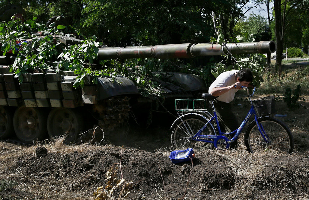 . A local resident passes by a cannon of a pro-Russian tank in the town of Novoazovsk,in eastern Ukraine, Friday, Aug. 29, 2014. In Novoazovsk, pro Russian rebel fighters looked to be in firm control, well-equipped and relaxed. At least half a dozen tanks were seen on roads around the town, although the total number at the rebelsí disposal is believed to be much greater. Novoazovsk fell swiftly to the rebels Wednesday after being pounded by shelling.(AP Photo/Sergei Grits)