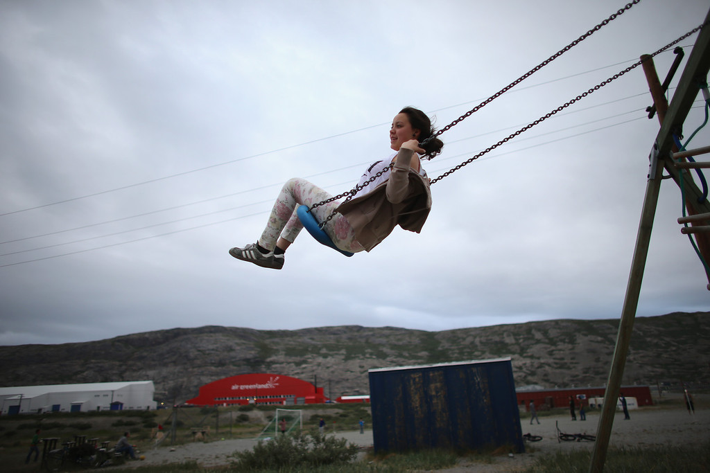 . Francica Olsem plays on a swing on July 09, 2013 in Kangerlussuaq, Greenland.  As Greenlanders adapt to the changing climate and go on with their lives, researchers affiliated with the National Science Foundation and other organizations are studying the occurrence of the melting glaciers and its long-term ramifications. In recent years, sea level rise in places such as Miami Beach has led to increased street flooding and prompted leaders such as New York City Mayor Michael Bloomberg to propose a $19.5 billion plan to boost the citys capacity to withstand future extreme weather events by, among other things, devising mechanisms to withstand flooding.  (Photo by Joe Raedle/Getty Images)