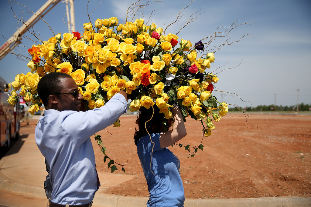 . Armand McCoy (L) and Jennifer Halstead carry a boquet of flowers past  empty land where the Moore Medical Center used to stand during the remembrance ceremony for the victims of last year\'s tornado and a ground breaking for the new medical center on May 20, 2014 in Moore, Oklahoma.  On May 20, 2013 a two-mile wide EF5 tornado touched down in the town killing 24 people and leaving behind extensive damage to homes and businesses.  (Photo by Joe Raedle/Getty Images)