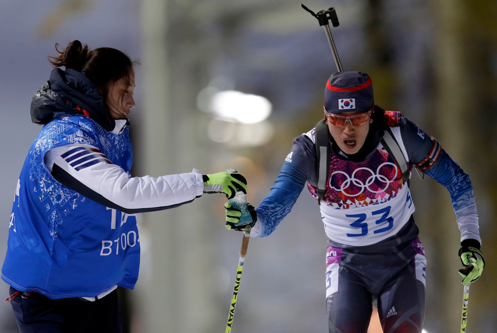 . South Korea\'s Lee In-bok is given a drink while competing in the men\'s biathlon 20k individual race, at the 2014 Winter Olympics, Thursday, Feb. 13, 2014, in Krasnaya Polyana, Russia. (AP Photo/Felipe Dana)