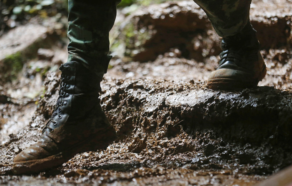 . In this Thursday, June 28, 2018, photo, a soldier walks through thick mud near the cave where a soccer team and their coach went missing in a large cave in Mae Sai, Chiang Rai province, in northern Thailand. (AP Photo/Sakchai Lalit)