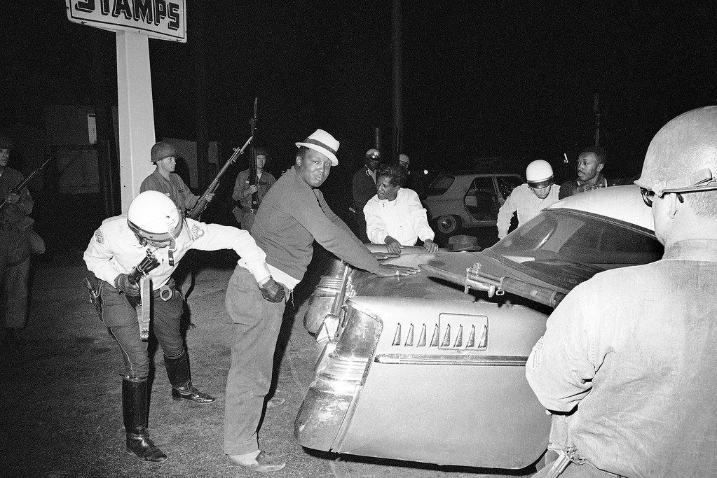 . City police search motorist who ventured into riot area of Cleveland, July 22, 1966. Violence and vandalism which ran rampant the last three nights appeared to be tapering off as police were reinforced by nearly 2,000 National Guardsmen. (AP Photo)