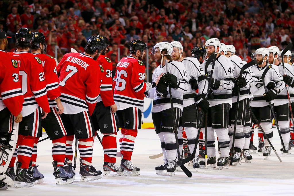 . The Los Angeles Kings (R) shake hands with the Chicago Blackhawks after the Blackhawks won Game 5 to take their NHL Western Conference final hockey playoff series in Chicago, Illinois, June 8, 2013. REUTERS/Jeff Haynes