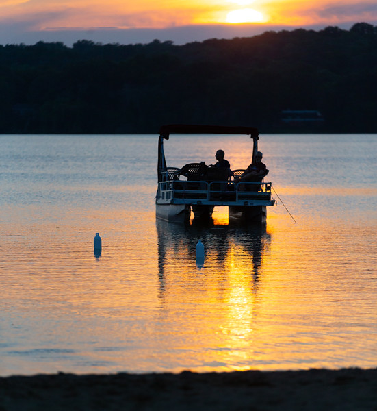 A pontoon boat enjoys a beautiful sunset at the Blues, Brews, and BBQ Friday, August 17, 2018 at Peterson Park in McHenry. KKoontz – For Shaw Media