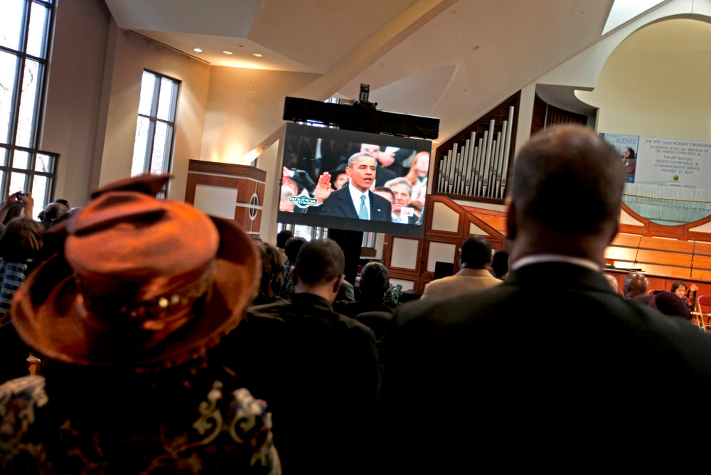 Description of . Parishioners watch as President Barack Obama is inaugurated following the Dr. Martin Luther King Jr. holiday commemorative service at the Ebenezer Baptist Church, Monday, Jan. 21, 2013, in Atlanta. The nation honors civil rights leader Martin Luther King Jr. on Monday, the same day as it celebrates the inauguration of the first black president to his second term. (AP Photo/David Goldman)