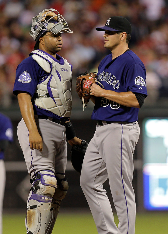. Colorado Rockies pitcher Jeff Manship confers with catcher Willin Rosario, left, after loading the bases in a baseball game against the Philadelphia Phillies, Monday, Aug. 19, 2013, in Philadelphia. (AP Photo/Laurence Kesterson)