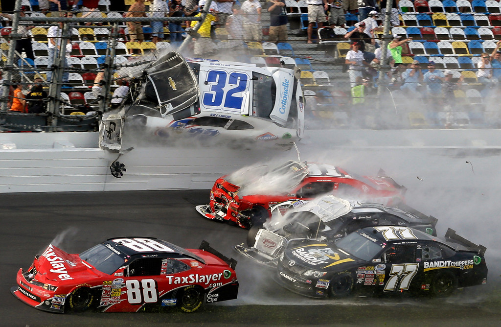 . Kyle Larson (32) goes airborne into the catch fence in a multi-car crash including  Dale Earnhardt Jr. (88), Parker Kilgerman (77), Justin Allgaier (31) and Brian Scott (2) during the final lap of  the NASCAR Nationwide Series auto race at Daytona International Speedway, Saturday, Feb. 23, 2013, in Daytona Beach, Fla. (AP Photo/John Raoux)