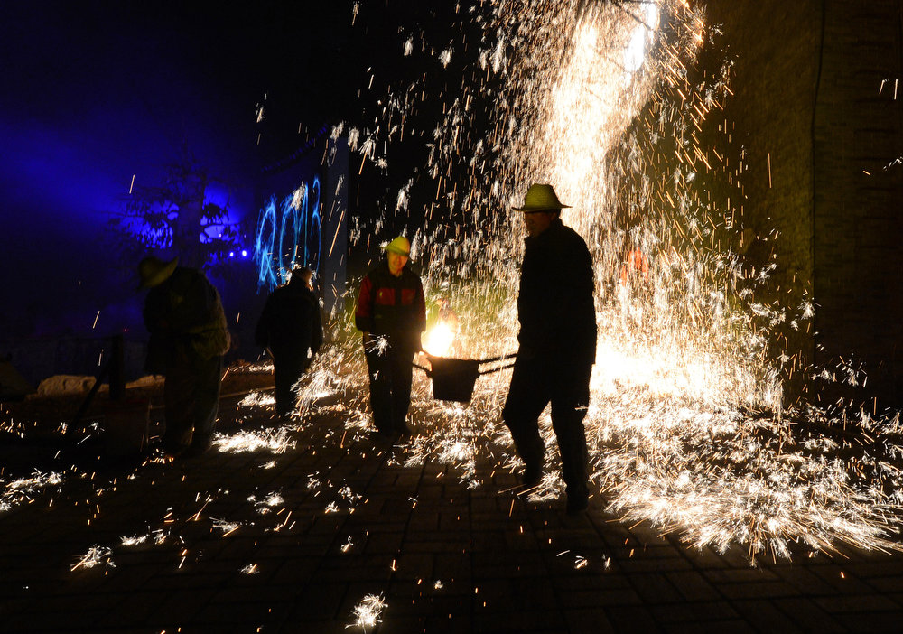 Description of . Chinese blacksmiths throw molten metal against a cold stone wall to create sparks, during the Lantern Festival which traditionally marks the end of the Lunar New Year celebrations, in Nuanquan, Hebei province on February 24, 2013.  For over 300 years, the village which is famous for its blacksmith skills, has maintained the tradition which they considered a cheaper alternative than buying fireworks during the Lantern Festival.    MARK RALSTON/AFP/Getty Images