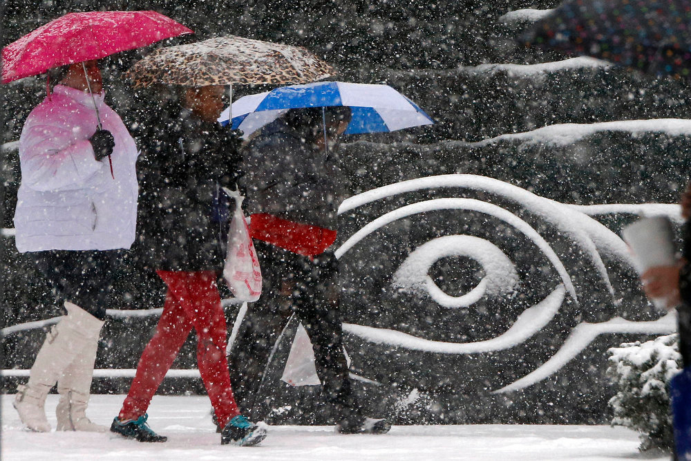 . A group walks past a downtown Pittsburgh sculpture as snow starts to fall Wednesday, Dec. 26, 2012. Forecasts call for 3-6 more inches of snow in Pittsburgh by Thursday morning. (AP Photo/Gene J. Puskar)