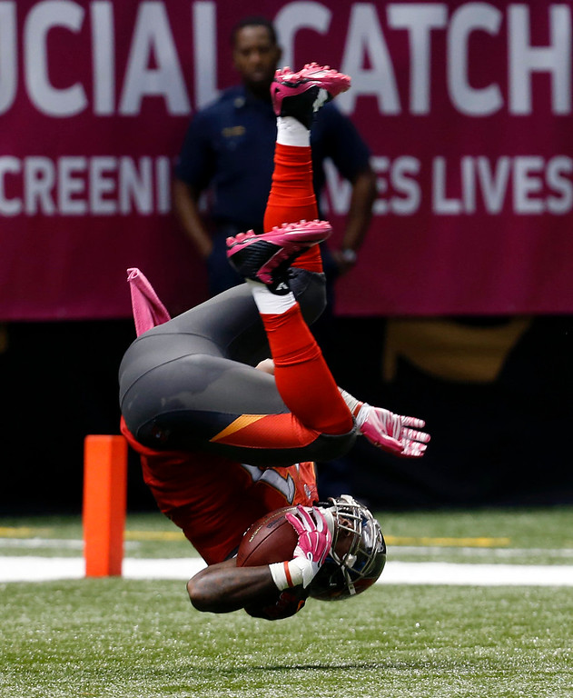 . Tampa Bay Buccaneers outside linebacker Danny Lansanah (51) does a flip as he crosses the goal line for a touchdown after he intercepted New Orleans Saints quarterback Drew Brees in the second half of an NFL football game in New Orleans, Sunday, Oct. 5, 2014. (AP Photo/Jonathan Bachman)